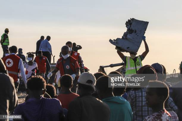A man carries a piece of debris on his head at the crash site of a Nairobibound Ethiopian Airlines flight near Bishoftu a town some 60 kilometres...