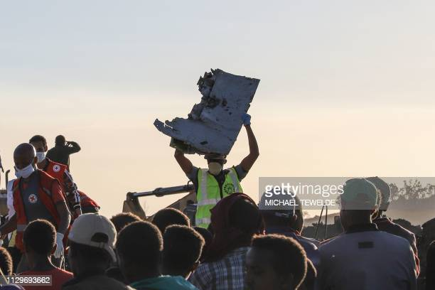 TOPSHOT A man carries a piece of debris on his head at the crash site of a Nairobibound Ethiopian Airlines flight near Bishoftu a town some 60...