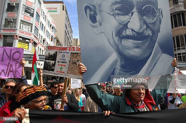 A man carries a placard depicting Gandhi to encourage peaceful protest during the 'Stop Bush Make Howard History Rally' held at Sydney Town Hall...