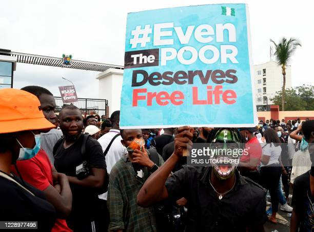 """Man carries a placard reading """"Even The Poor Deserves Free Life"""" on the road to a government house in continuation of ongoing demonstrations to call..."""