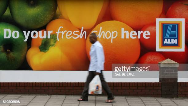 A man carries a plastic shopping bag as he walks past an Aldi supermarket store in London on September 26 2016 Aldi UK announced on Monday that it...