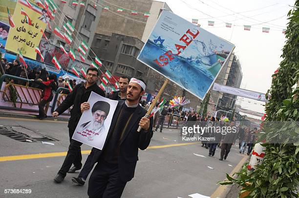 Man carries a poster with a photo of Iran's supreme leader Ayatollah Ali Khamenei while holding up an anti Israeli banner while marching on...