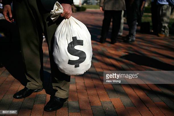 A man carries a props money bag during a rally at the Lafayette Square March 9 2009 in Washington DC The rally was held to support the Employee Free...