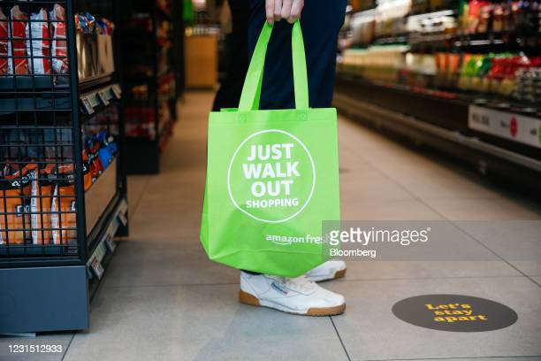 Man carries a reusable shopping bag as he shops at the Amazon.com Inc. Amazon Fresh cashierless convenience store in the Ealing area of London, U.K.,...