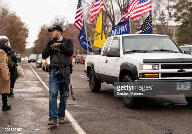 Man carries a rifle as supporters of President Donald Trump gather for a rally outside the Governor's Mansion on November 14, 2020 in St Paul,...