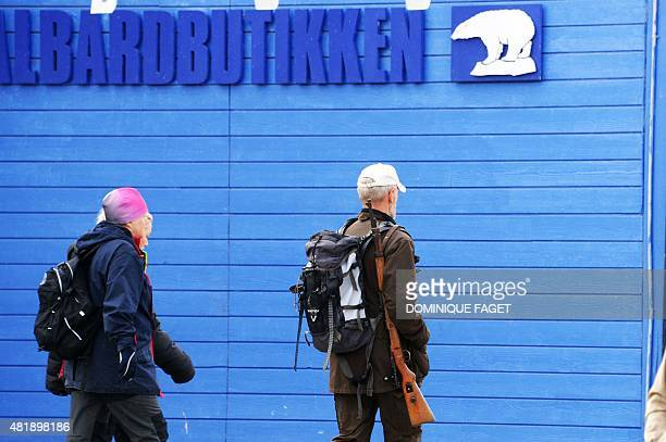 A man carries a rifle on July 24 2015 as he walks in the center of Longyearbyen a community counting 3000 polar bears where authorities of the...