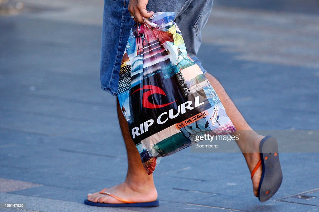 A man carries a Rip Curl-branded shopping bag as he walks through the Manly area of Sydney, Australia, on Sunday, May 19, 2013. The Reserve Bank of Australia cut its benchmark interest rate to a record low this month to boost businesses weakened by the currency's sustained strength, even as households reacted to earlier reductions. Photographer: Brendon Thorne/Bloomberg via Getty Images