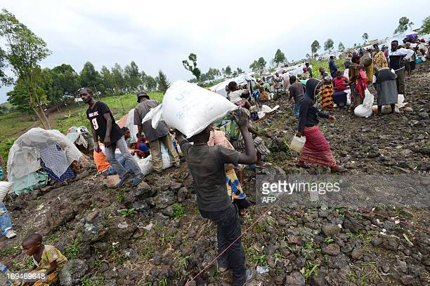 A man carries a sac on his head during a food distribution program at an Internally Displaced People camp in Mugunga 15km outside of Goma on May 25...