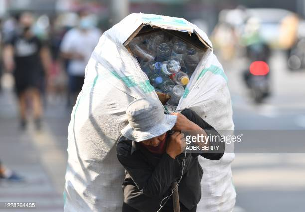 Man carries a sack full of plastic bottles for recycling in Jakarta on August 30, 2020.