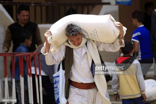A man carries a sack of food aid distributed on displaced people who fled battles in Saada province and other war affected areas in Yemen at a school...