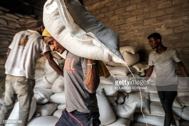 Man carries a sack of wheat during a food distribution in Ataye, Ethiopia, on May 15, 2021. - More than 100 civilians died in a recent flare-up of...