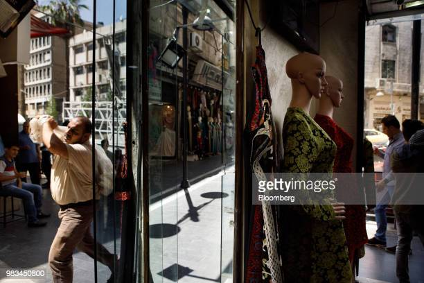 A man carries a sack past a women's fashion store in Amman Jordan on Thursday June 21 2018 President Trump and First Lady Melania Trump will host...