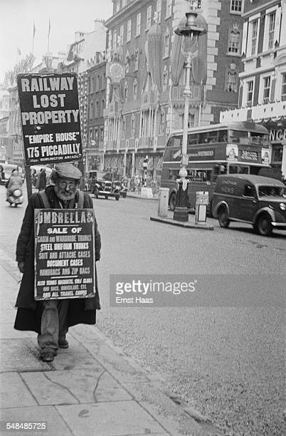 A man carries a sandwich board advertising lost property for sale Mayfair London circa 1953