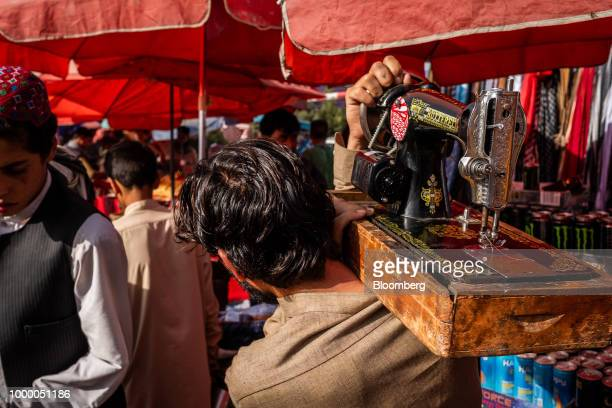 A man carries a sewing machine on his shoulder through a market in Kabul Afghanistan on Thursday July 12 2018 US President Donald last year said...