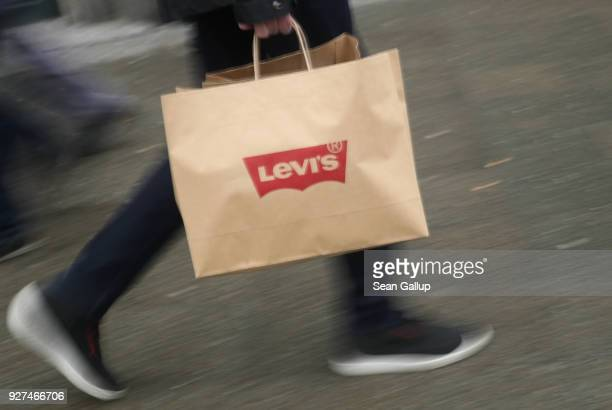 PA man carries a shopping bag from a Levi's jeans and clothing store on March 5 2018 in Berlin Germany Tensions between US President Donald Trump and...