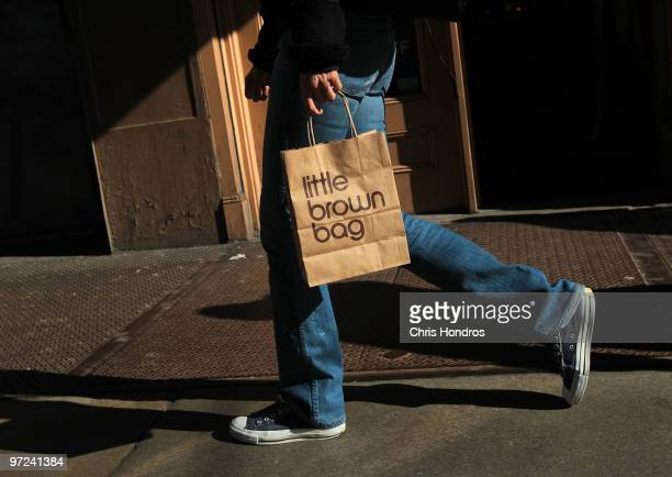A man carries a shopping bag from the Bloomingdale's store in the SoHo shopping district of Manhattan March 1 2010 in New York City Consumer spending...