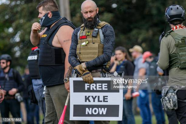 A man carries a sign advocating for the accused killer Kyle Rittenhouse in Wisconsin as the Proud Boys a rightwing proTrump group gather with their...