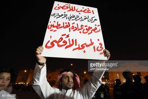 A man carries a sign with a slogan reading in Arabic 'the National Liberation Movement of Ahwaz supports the right of worship of Palestinians in...