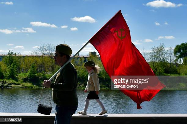 TOPSHOT A man carries a Soviet flag during Victory Day celebrations in the town of Pinsk some 305 km southwest of Minsk on May 9 2019