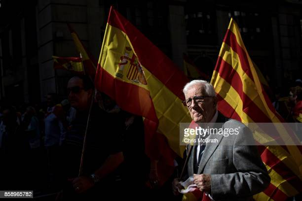 A man carries a Spanish national flag as he takes during a protest against Catalonia's indepedence on October 8 2017 in Barcelona Spain Large numbers...