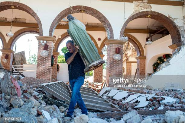 TOPSHOT A man carries a St Jude statue from the Inmaculada Concepcion church ruins that was built in 1841 and collapsed after an earthquake hit the...