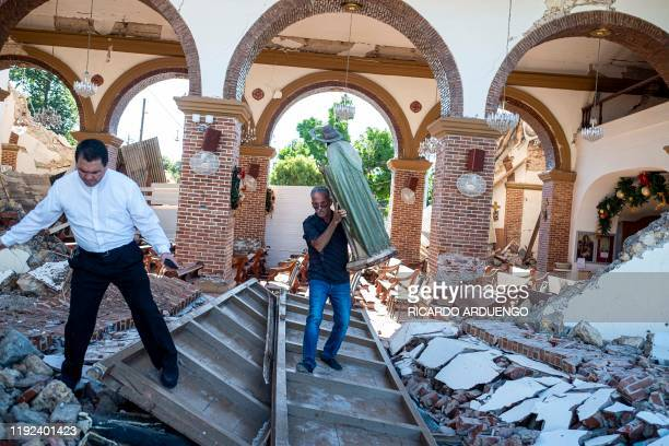 A man carries a St Jude statue from the Inmaculada Concepcion church ruins that was built in 1841 and collapsed after an earthquake hit the island in...
