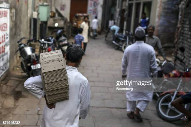 A man carries a stack of punched design templates on his shoulder while walking through the streets in Varanasi Uttar Pradesh India on Saturday Oct...