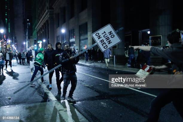 A man carries a traffic signal as Philadelphia Eagles fans celebrate victory in Super Bowl LII game against the New England Patriots on February 4...