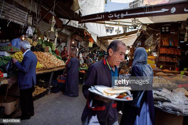 A man carries a tray of flat breads through a local market in downtown Amman Jordan on Thursday June 21 2018 President Trump and First Lady Melania...