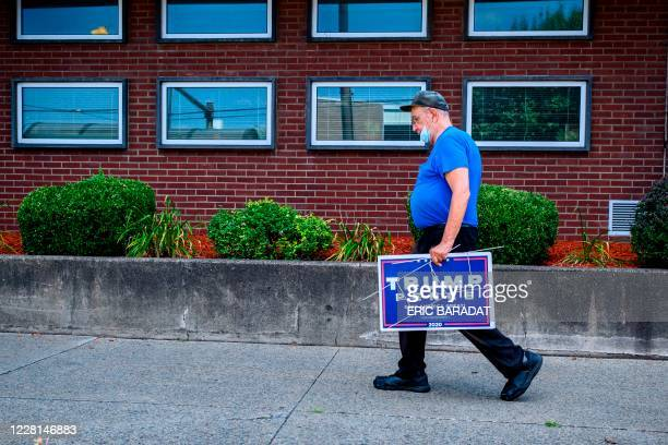 """Man carries a """"Trump"""" sign as he walks in the downton part of Scranton, Pennsylvania, the """"Electric City"""" on August 11, 2020. - It is not hard to..."""