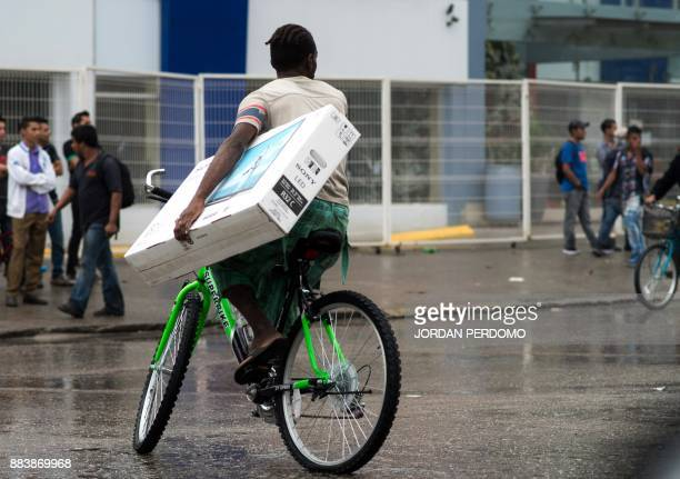 A man carries a TV set looted from a shop as supporters of Honduran presidential candidate for the Opposition Alliance against the Dictatorship...