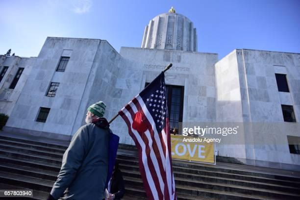 A man carries a US flag in front of the State Capitol during a show of love against a proTrump 'Make America Great Again' rally in Salem Oregon...