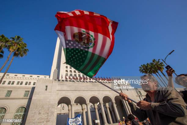 Man carries a U.S.flag and a flag of Mexico together as people march and rally on May Day, also known as International Workers Day, on May 1, 2019 in...