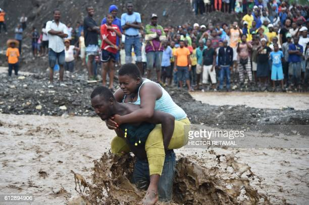 TOPSHOT A man carries a woman across a river at Petit Goave where a bridge collapsed during the rains of the Hurricane Matthew southwest of...