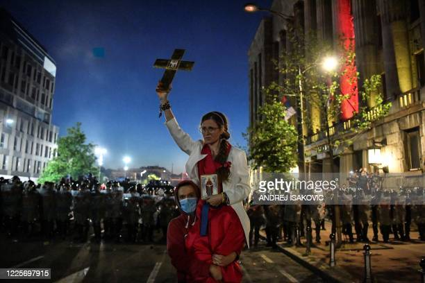 Man carries a woman holding up a Christian cross in front of riot police as clashes erupt in central Belgrade on July 8, 2020 between police and...