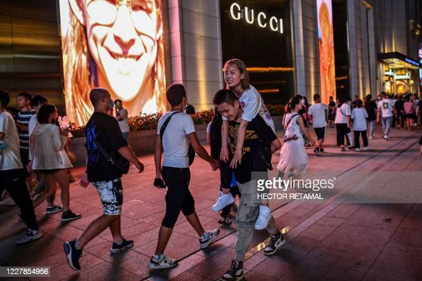 Man carries a woman piggyback on a street surrouned by shops and malls in Shanghai on July 31, 2020.