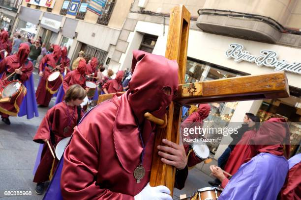 A man carries a wooden cross on his shoulder while marching with people of the brotherhoods or neighborhoods dressed in red habits and hoods in the...