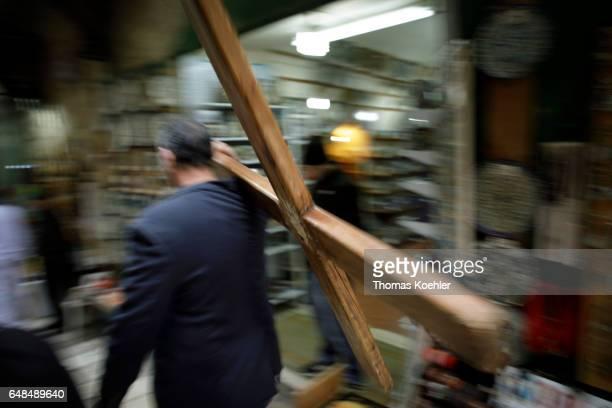 A man carries a wooden cross on Via Dolorosa street scene in the historic city center of Jerusalem on February 08 2017 in Jerusalem Israel