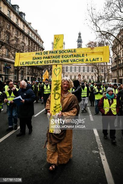 A man carries a wooden cross with the words 'No social peace without equal sharing the people is not a milk cow' in a street of Paris on January 5...