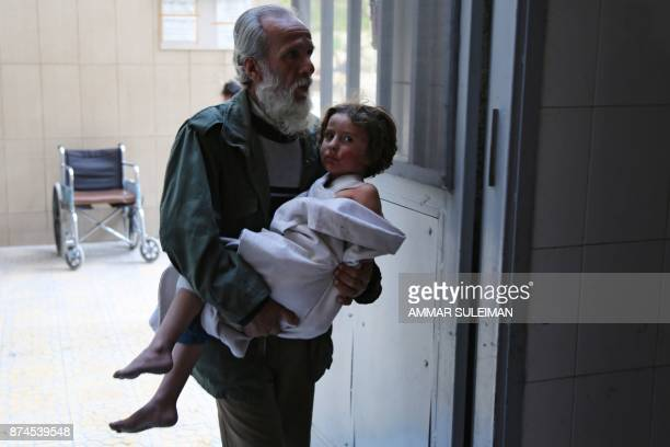 TOPSHOT A man carries a wounded child into the emergency ward of a hospital in the Eastern Ghouta town of Kafr Batna on the outskirts of Damascus...