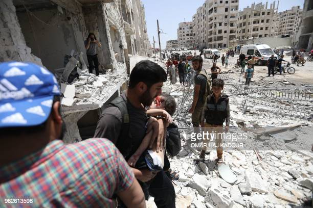 TOPSHOT A man carries a wounded child out of a building following a car bomb explosion in the northern Syrian city of Idlib on May 26 2018