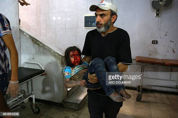 A man carries a wounded girl at a make shift hospital in the rebelheld area of Douma east of the capital Damascus following shelling and air raids by...