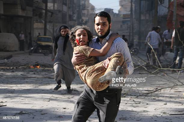 A man carries a wounded girl following a reported bombardment with explosivepacked 'barrel bombs' by Syrian government forces in the AlMowasalat...