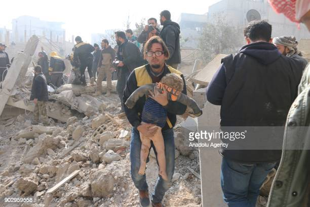 A man carries a wounded kid during the search and rescue operation at the debris of a building after warplanes belonging to Assad Regime carried out...