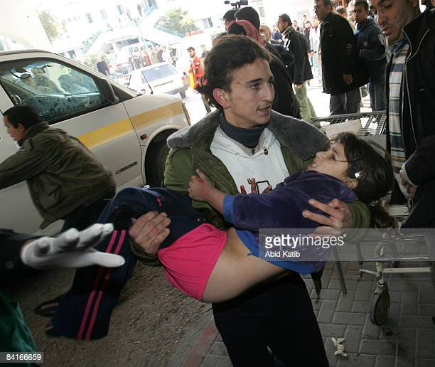A man carries a wounded Palestinian girl into a hospital in Gaza January 4 2009 Israeli shells killed at least 12 Palestinian civilians and wounded...