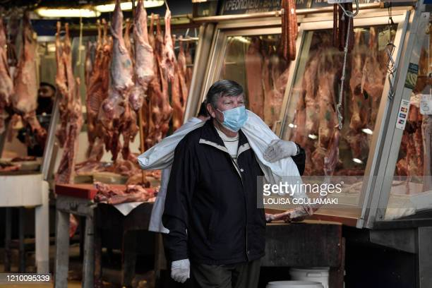 TOPSHOT A man carries a wrapped piece of lamb as he walks through Athen's main meat market on April 16 2020 ahead of the Greek Orthodox Easter this...