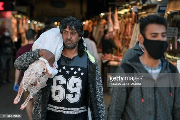 A man carries a wrapped piece of lamb over his shoulder as he walks through Athen's main meat market on April 16 2020 ahead of the Greek Orthodox...