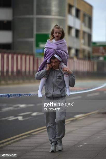 A man carries a young girl on his shoulders near Victoria station in Manchester northwest England on May 23 2017 Twenty two people have been killed...
