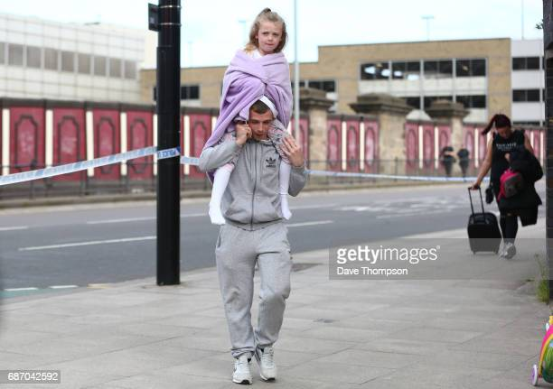 A man carries a young girl on his shoulders on May 23 2017 in Manchester England An explosion occurred at Manchester Arena as concert goers were...