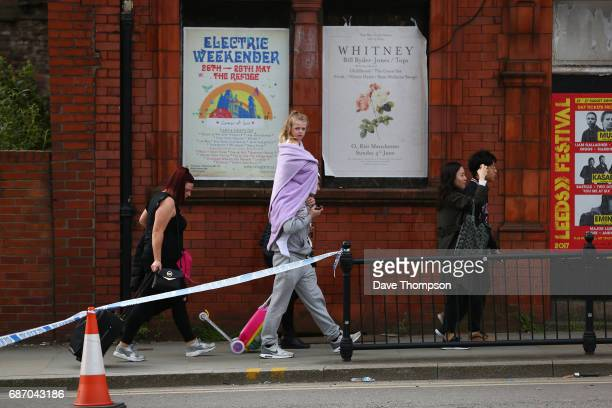 A man carries a young girl on his shoulders the morning after a terrorist attack on May 23 2017 in Manchester England An explosion occurred at...